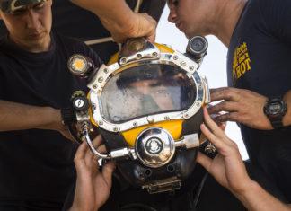 Marineduiker krijgt hulp bij het opzetten van zijn helm