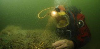 Een duikende archeoloog van de RCE aan het werk bij een wrak in de Waddenzee bij Burgzand