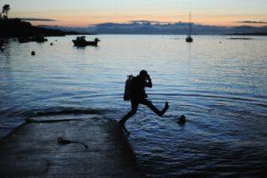 Duiker springt van pier - nachtduik - Foto: Nick Birse